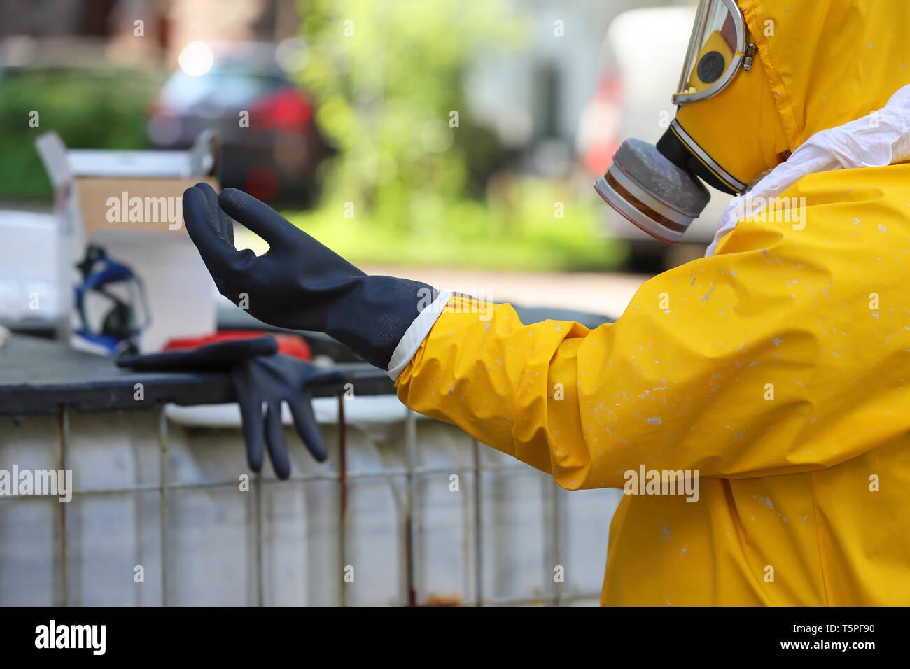 Lavoratore con indumenti protettivi guanti mette su Immagini Stock