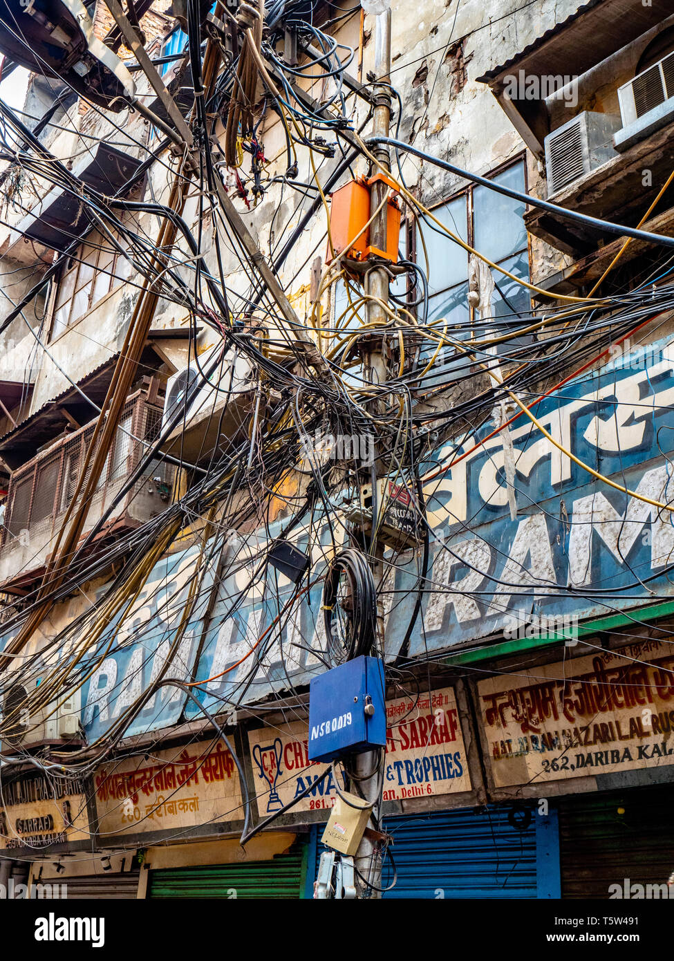 Caotico groviglio di fili per illuminazione stradale le forniture di elettricità e i cavi telefonici in una strada della città vecchia di Delhi India del Nord Immagini Stock