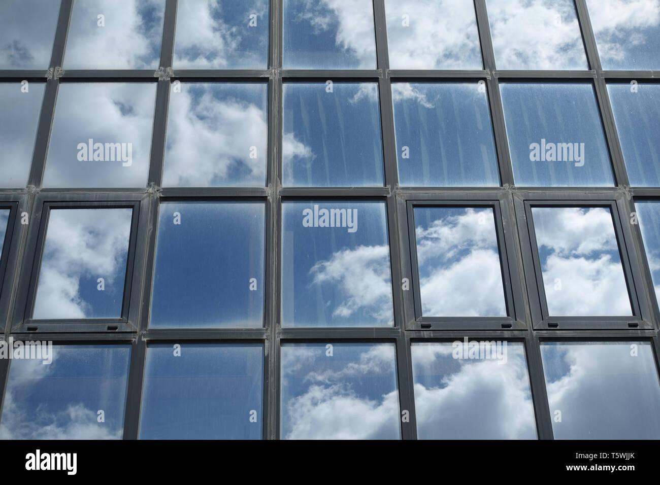 Cielo blu e nuvole bianche si riflette sulle finestre sporche. Office facciata di edificio closeup abstract background. Foto Stock