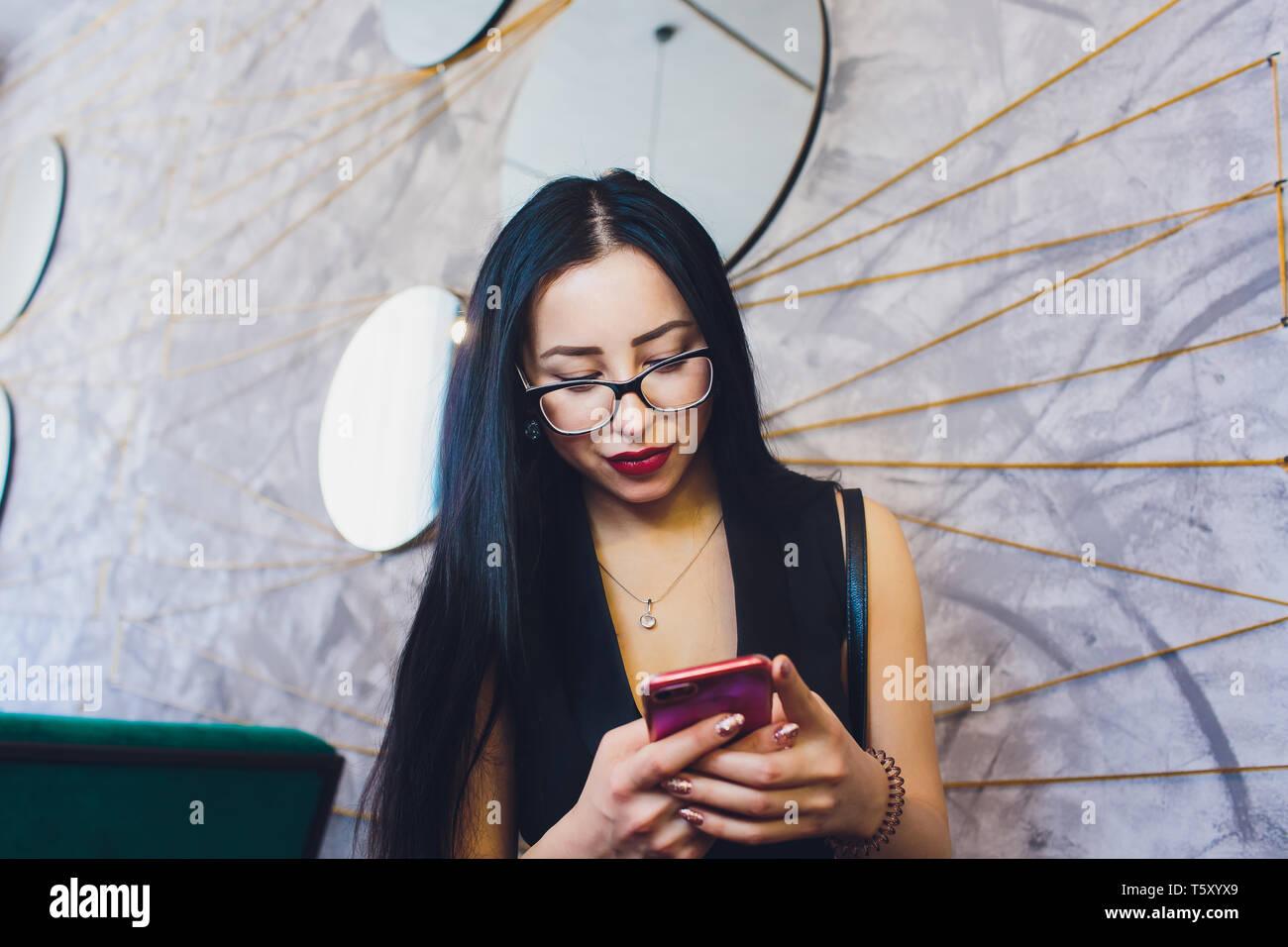 Felice ragazza araba utilizzando smart phone su un muro di mattoni. Donna sorridente con capelli ricci in abiti casual in background urbano. Foto Stock