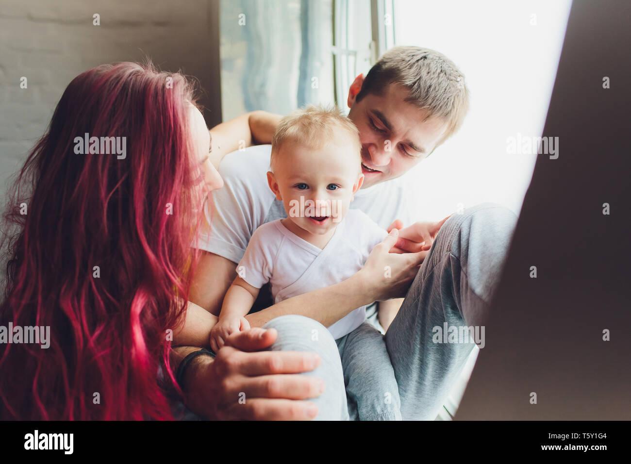 La famiglia felice della madre, padre e figlio figlio di giocare e coccole a casa sul pavimento vicino a una grande finestra. Foto Stock