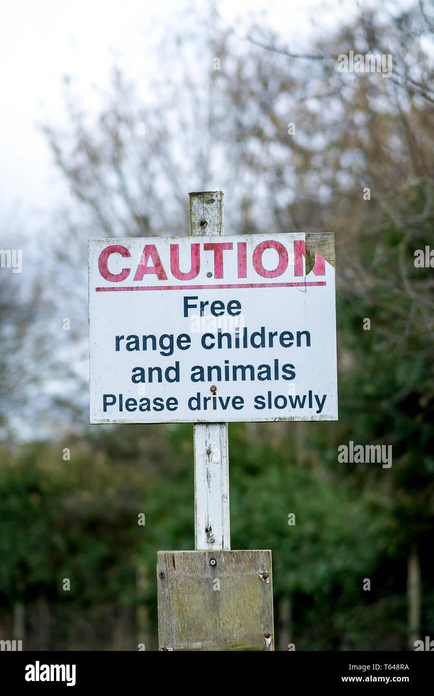 Avviso pubblico avviso per gli automobilisti si prega di guidare lentamente a causa della gamma gratuita I bambini e gli animali nella zona. Buoni consigli britannici con senso dell'umorismo! Immagini Stock