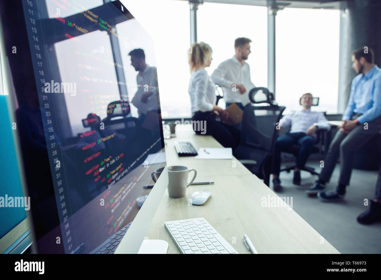 Close-up del posto di lavoro in un ufficio moderno con la gente di affari dietro. I colleghi riuniti per discutere i loro futuri piani finanziari. Foto Stock