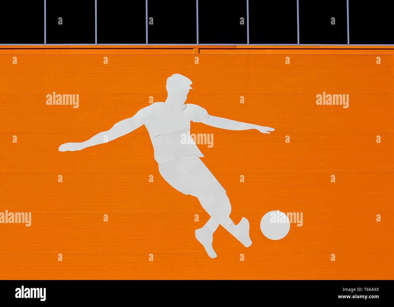 L'applicazione sotto forma di un giocatore di football sulla parete esterna di un impianto sportivo Immagini Stock