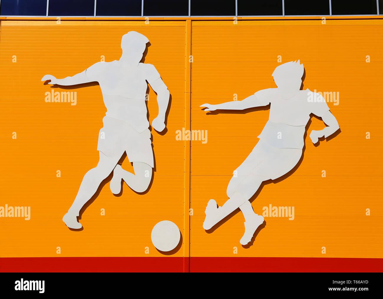 Applicazione in forma di giocatori di calcio sulla parete esterna di un impianto sportivo Immagini Stock