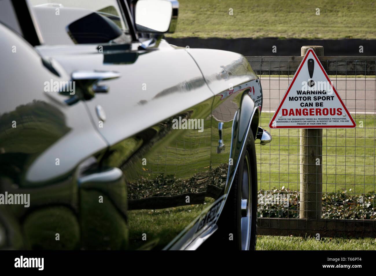 Avvertenza Motor Sport può essere pericoloso segno sulla recinzione di terra lungo il rettilineo Lavant area di visualizzazione al 77th Goodwood GRRC Assemblea dei Soci, REGNO UNITO Immagini Stock