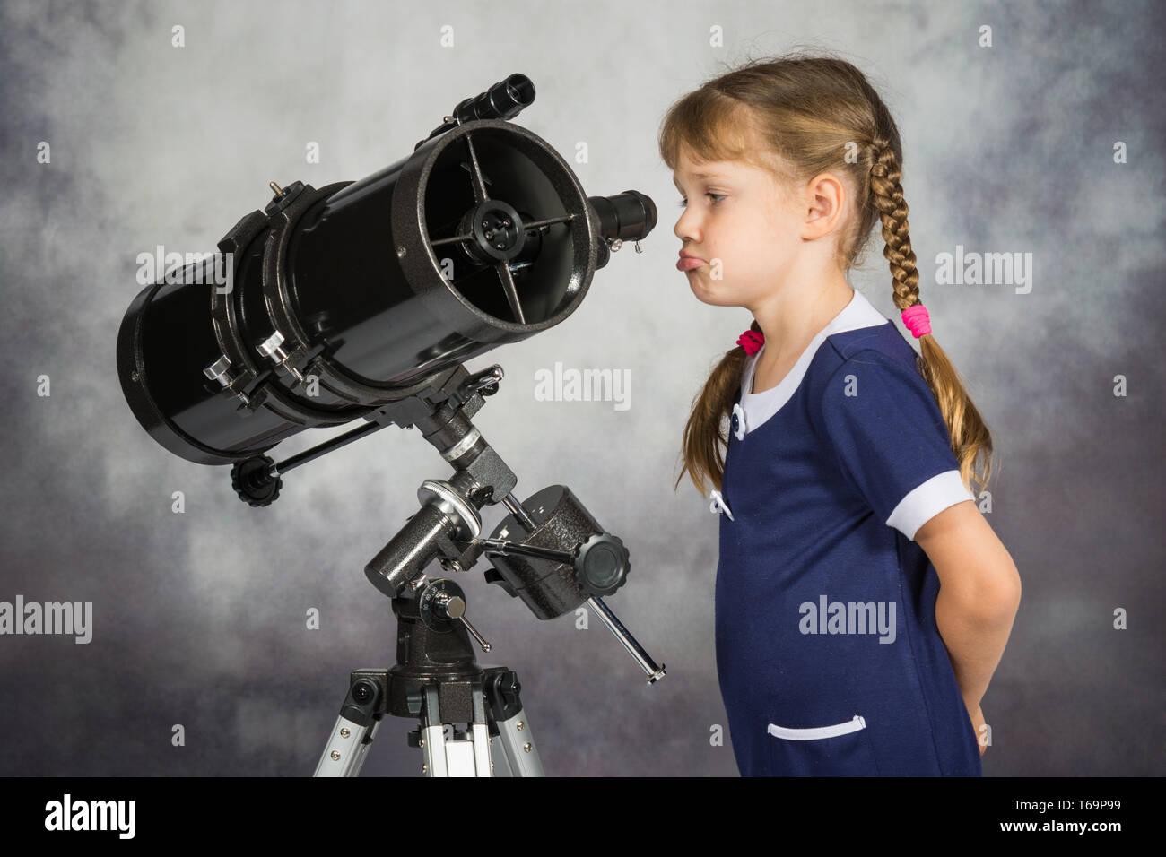 Ragazza deluso da ciò che egli vedeva nel telescopio Immagini Stock