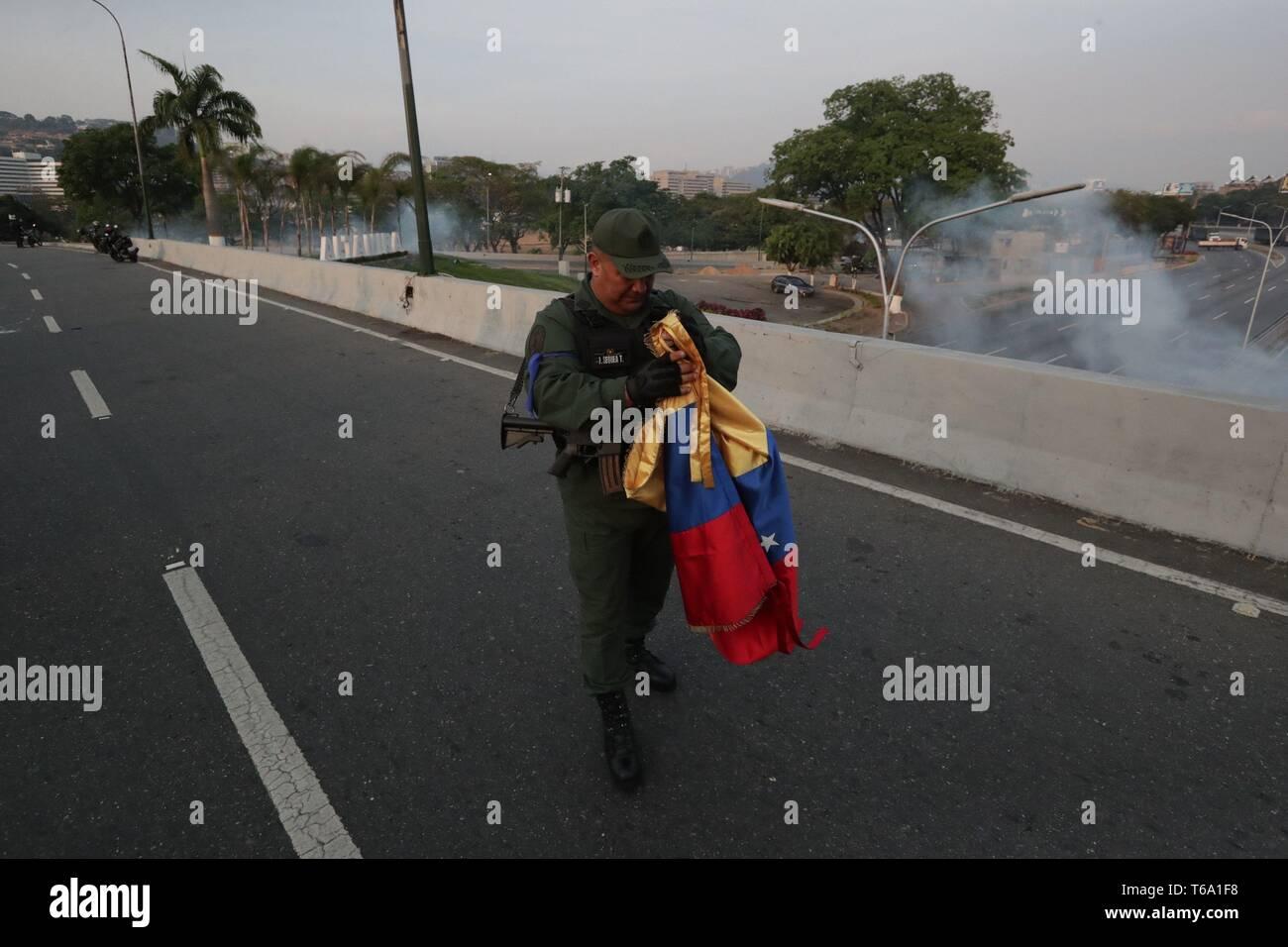Caracas, Venezuela. 30 apr, 2019. Un soldato venezuelano detiene un venezuelano bandiera nazionale a La Carlota base, dove oppositore venezuelano Leopoldo Lopez (invisibile) è stato portato a soddisfare con il presidente ad interim Juan Guaido dopo egli essendo rilasciato dalla sua casa, nell'Est di Caracas, Venezuela, 30 aprile 2019. Lopez, che era agli arresti domiciliari, è stata rilasciata la mattina presto il 30 aprile da un movimento di opposizione. Credito: Rayneri Pena/EFE/Alamy Live News Immagini Stock