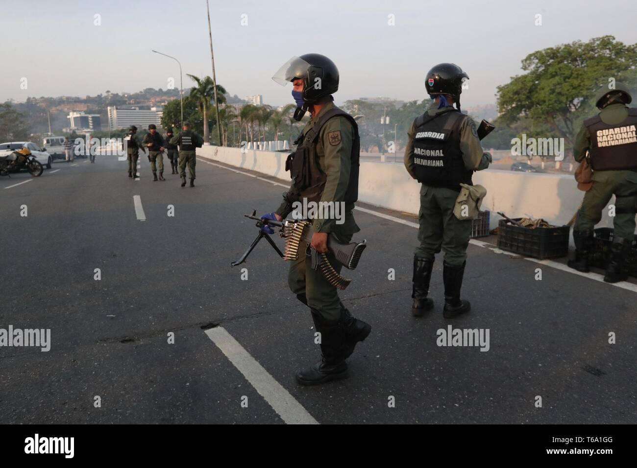 Caracas, Venezuela. 30 apr, 2019. Molti soldati venezuelano guardia a La Carlota base, dove oppositore venezuelano Leopoldo Lopez (invisibile) è stato portato a soddisfare con il presidente ad interim Juan Guaido dopo egli essendo rilasciato dalla sua casa, nell'Est di Caracas, Venezuela, 30 aprile 2019. Lopez, che era agli arresti domiciliari, è stata rilasciata la mattina presto il 30 aprile da un movimento di opposizione. Credito: Rayneri Pena/EFE/Alamy Live News Immagini Stock
