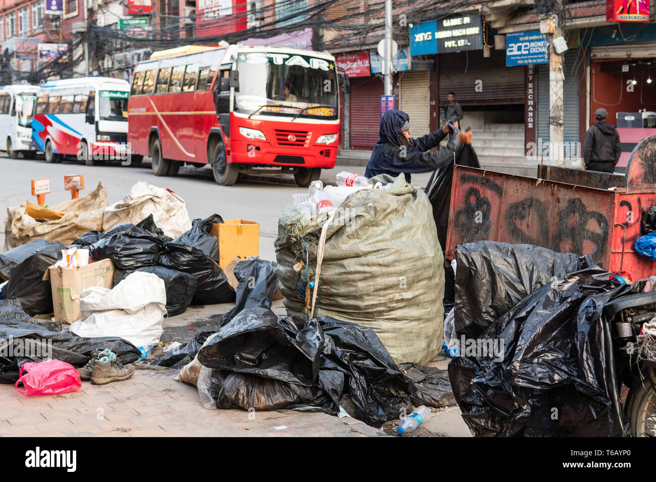 Kathmandu, Nepal - Aprile 20th, 2019 - garbage collector ordinamento tramite cumuli di rifiuti nelle prime ore del mattino in strada. Immagini Stock
