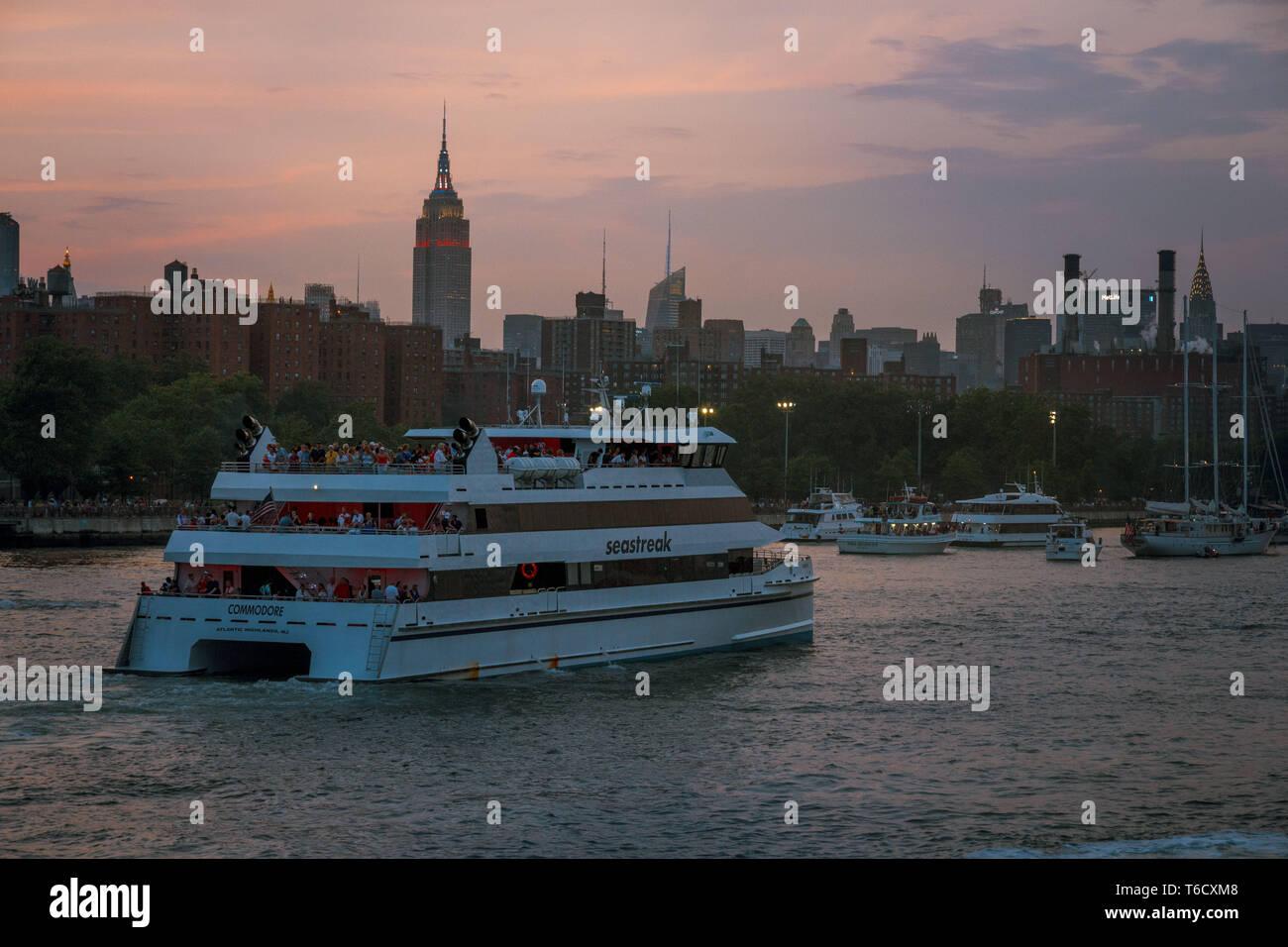 Sonnenuntergang und Boote auf dem East River unter der Brücke am 04.07.2018 zum Unabhängigkeitstag / Tramonto nave su East River sotto il ponte Foto Stock
