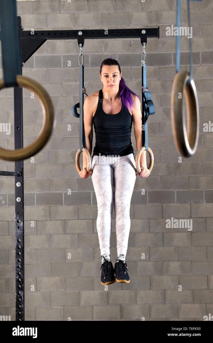 Donna giovane atleta facendo muscolo su esercitazioni sul ring durante il suo allenamento in palestra in una lunghezza piena vista frontale sollevato su bracci estesi Foto Stock