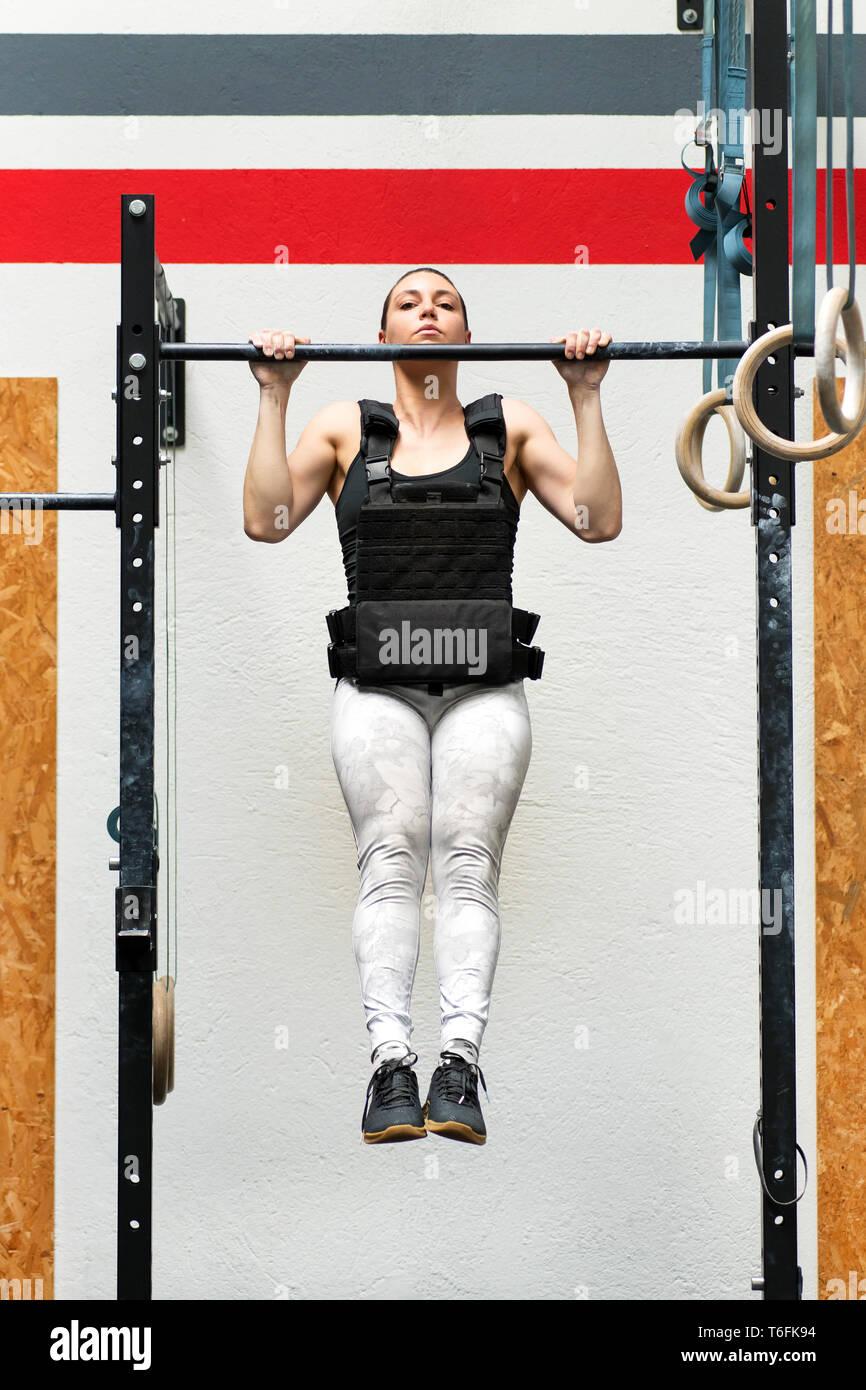 Donna giovane atleta ponderata facendo pull-up su una barra che indossa una giacca pesante per rafforzare il suo corpo superiore muscoli in salute e concetto di fitness Immagini Stock