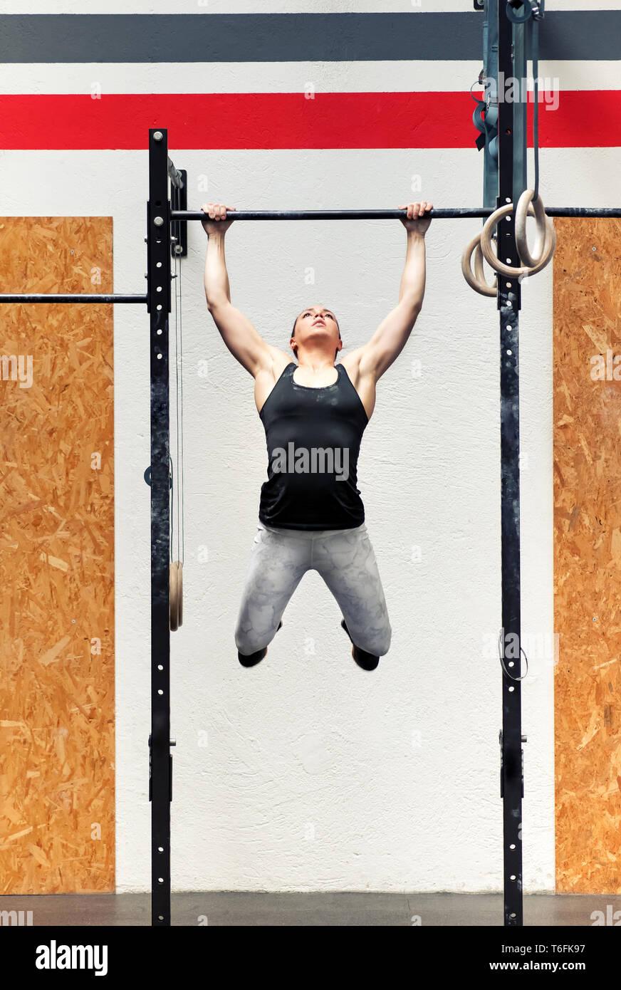 Giovani montare forte ragazza muscolare atleta facendo pull-up su una barra durante il suo allenamento in piena vista frontale all'interno di una palestra professionale Immagini Stock