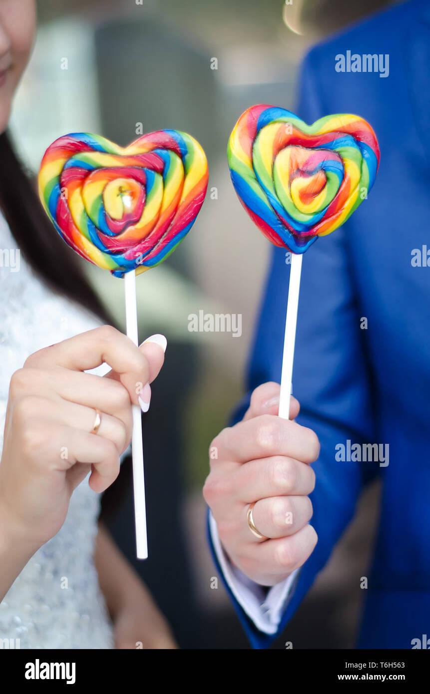 Dolci caramelle colorate cuori su bastoni nelle mani dello sposo e della sposa Foto Stock