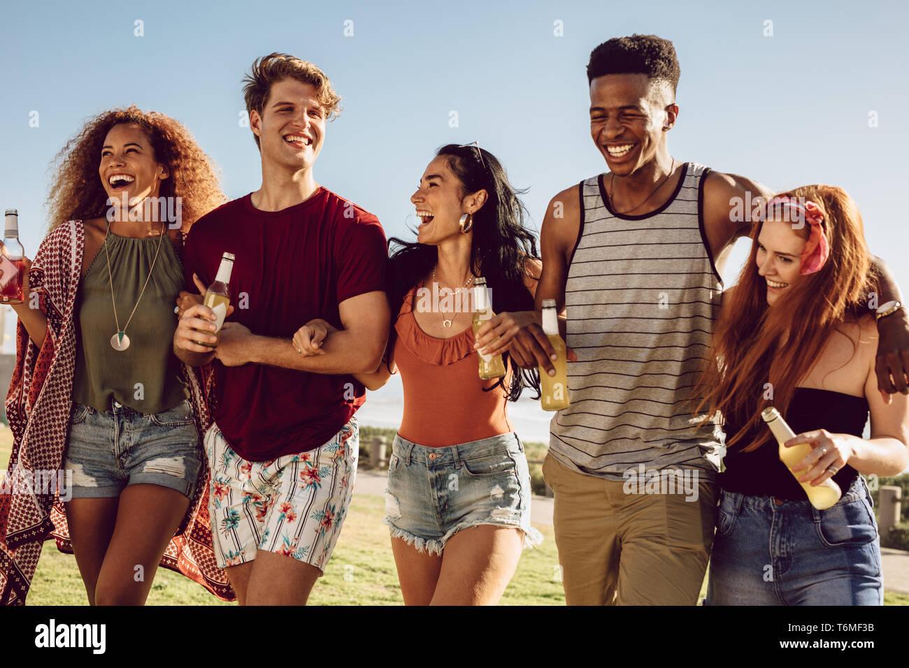 Gruppo di amici camminare insieme con bracci di bloccaggio. Giovani uomini e donne con birre camminare insieme e divertirsi. Foto Stock