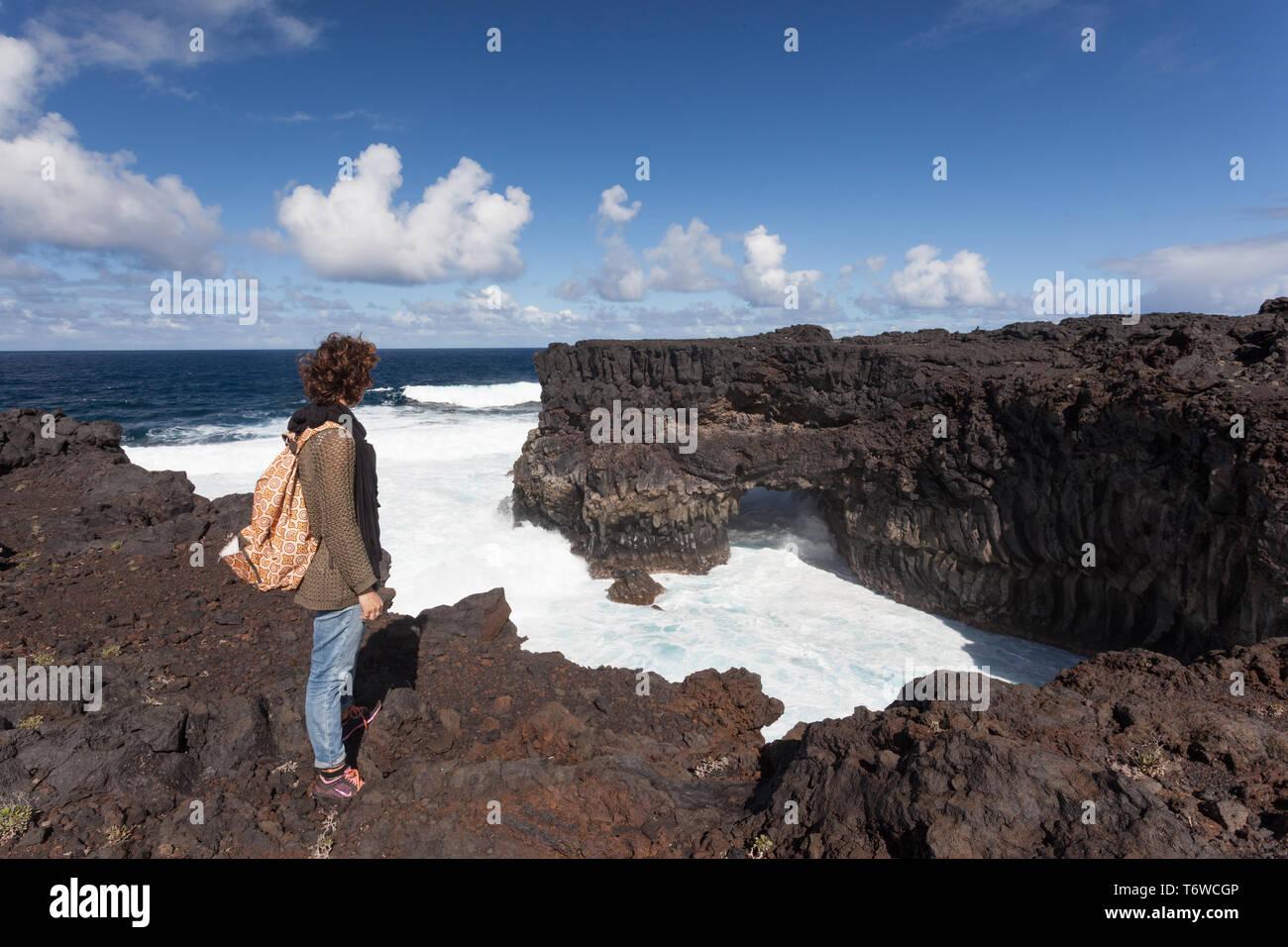 20 30 anni ragazza in piedi su una scogliera con big surf sotto Immagini Stock