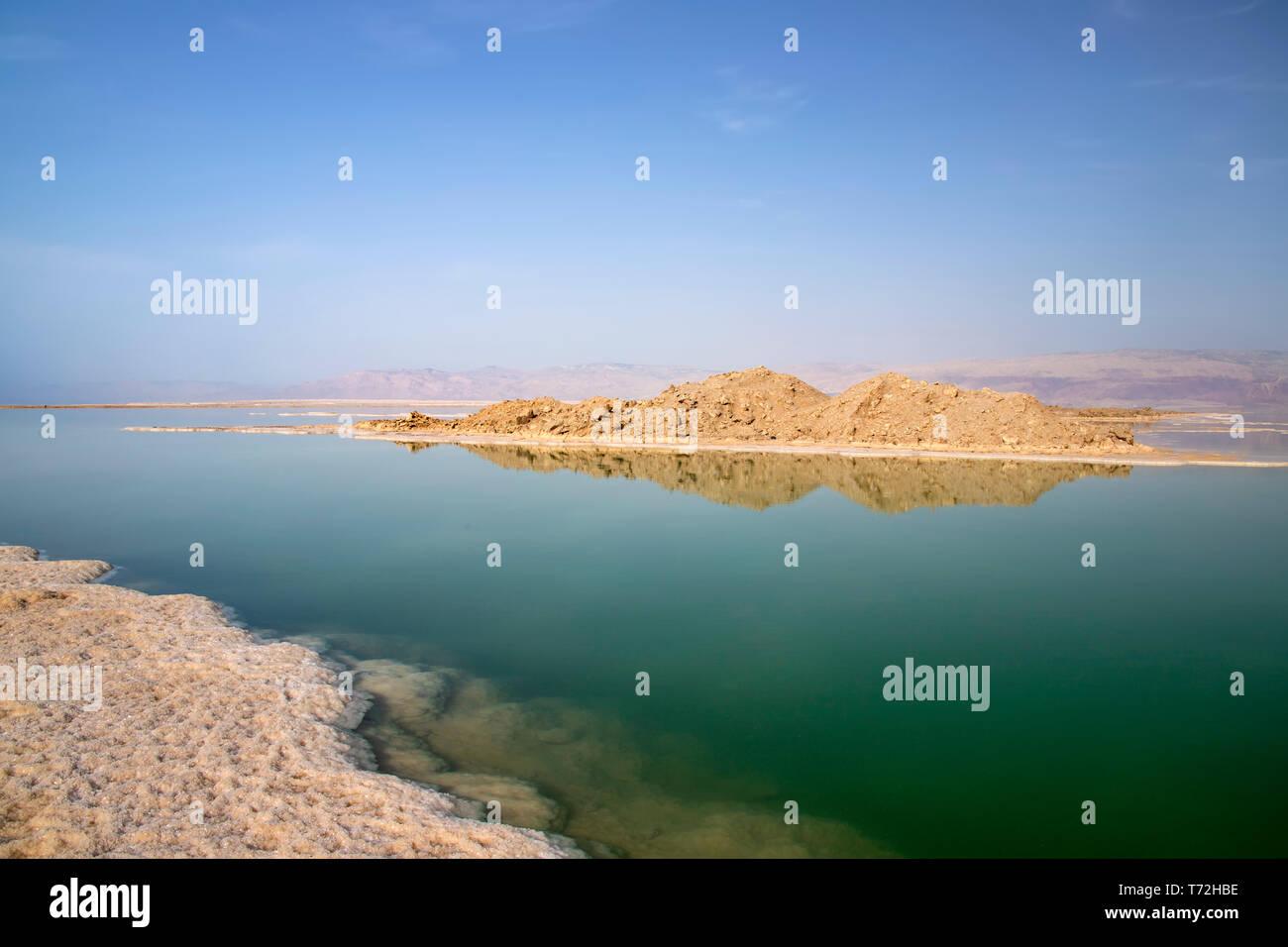 La riflessione di colline in acqua salata del Mar Morto sotto il quale sale formazioni sono visibili Foto Stock