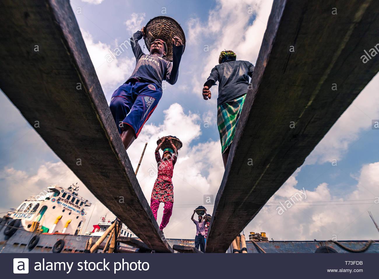 Maschio e femmina di lavoratori portuali sono visti come essi lo scarico del carbone con bambù cestini da traghetti a fiume Buriganga port a Dhaka, nel Bangladesh. Immagini Stock