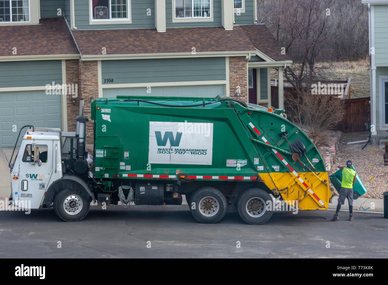 Una gestione dei rifiuti lavoratore verde si Svuota cestino in plastica contenitori in una zona residenziale, Castle Rock Colorado US. Foto scattata in aprile. Immagini Stock
