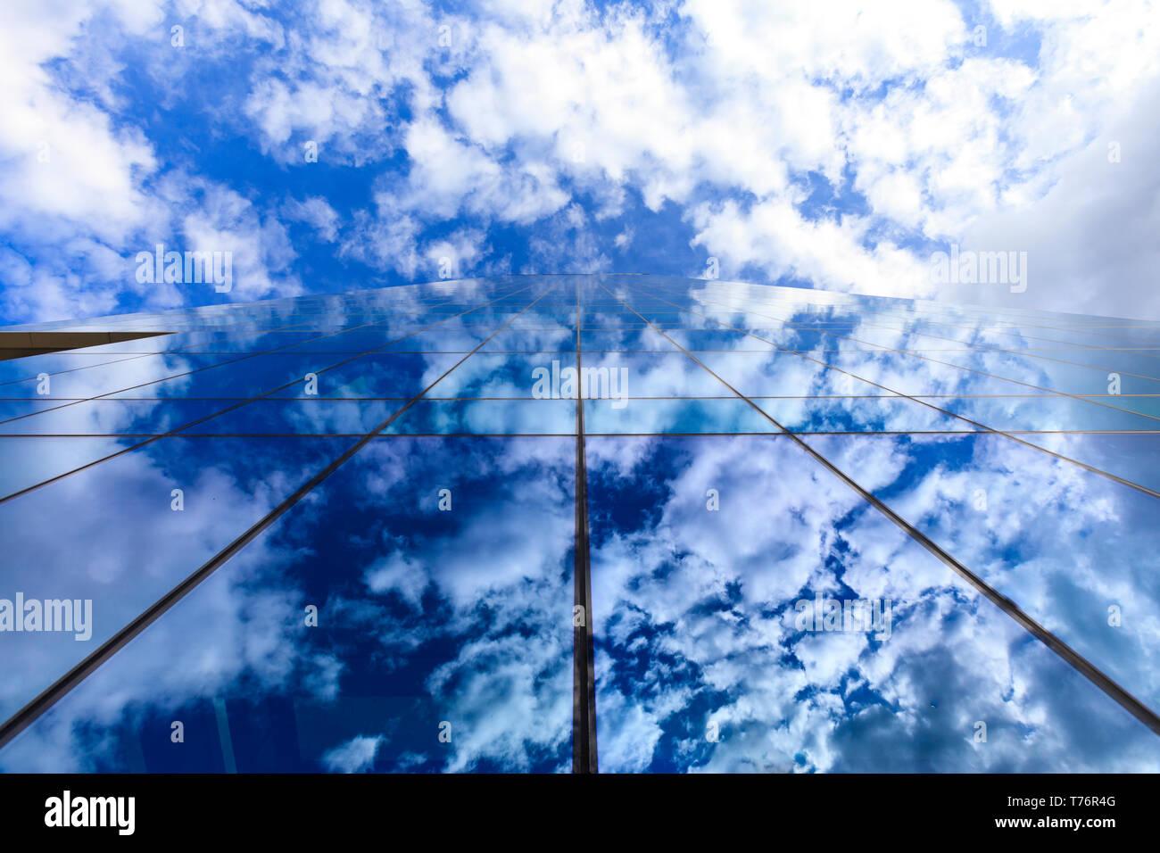 Nuvole e cielo blu riflessa sul vetro edificio per uffici di windows Foto Stock