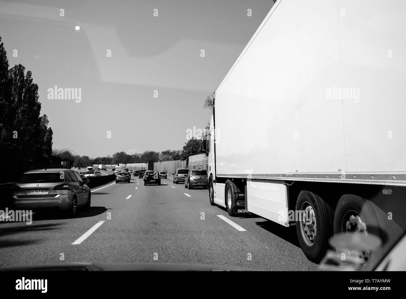Francia - Apr 19, 2019: bianco e nero moderare il traffico su autostrada francese in prospettiva a lungo l'autostrada con auto, camion e SUV Immagini Stock