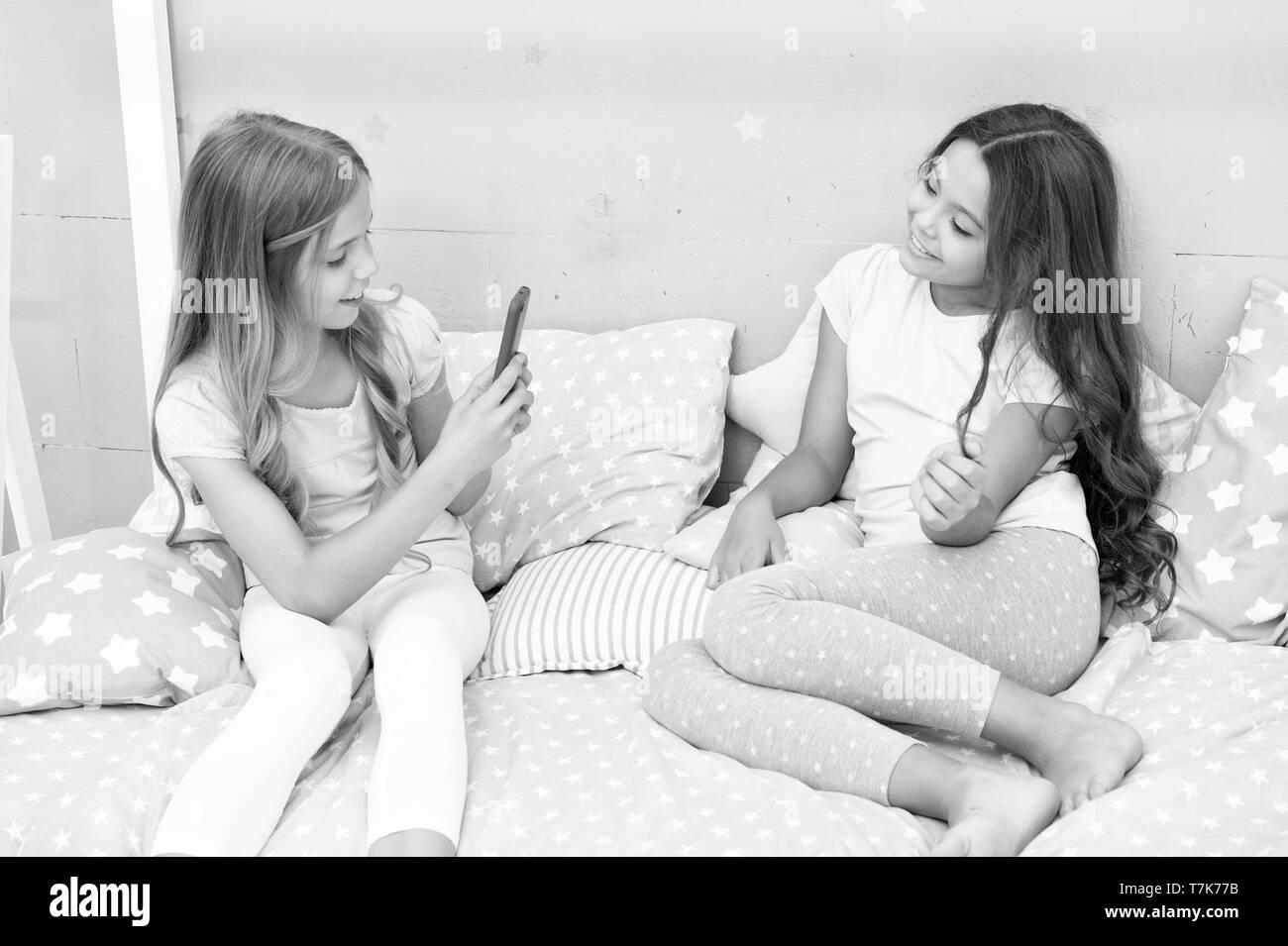 Streaming Online vlog channel. Sorelle in pigiama camera da letto potrete rilassarvi e prendere foto divertenti per il social network account. Svago e divertimento. Reti sociali di concetto. Ragazze amici prendendo la foto per le reti sociali. Immagini Stock