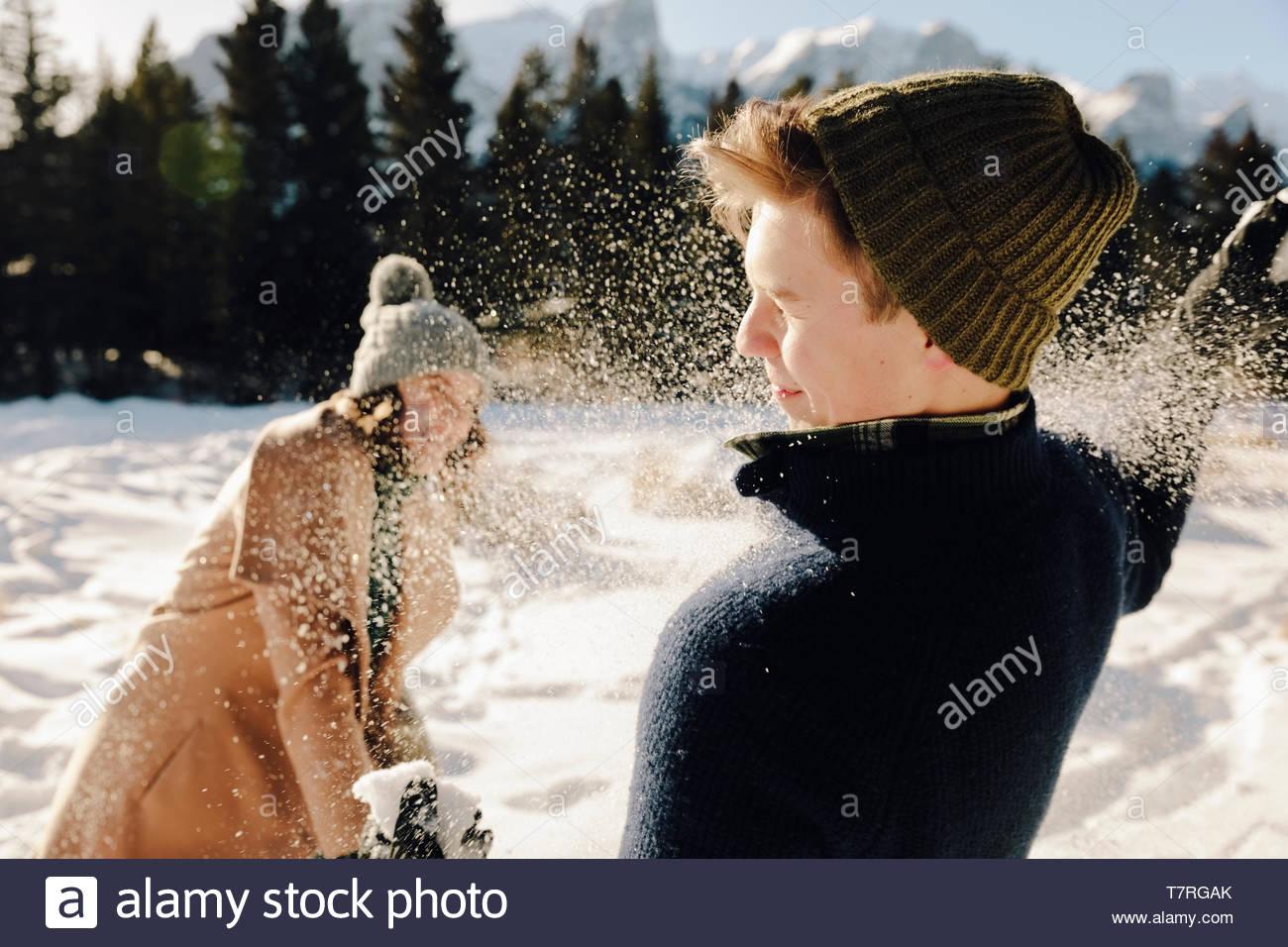 Giocoso coppia giovane godendo lotta con le palle di neve Immagini Stock