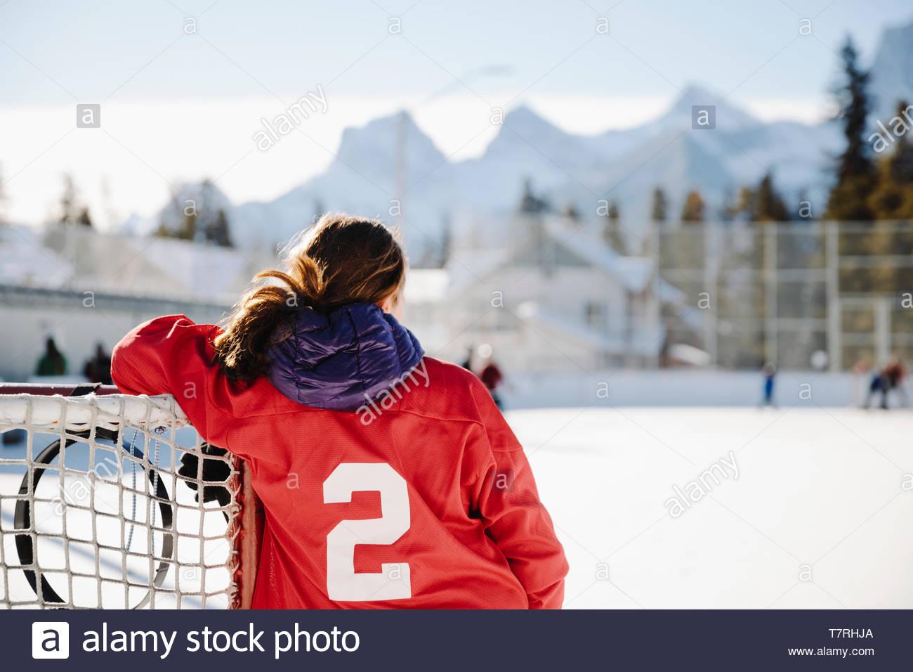 Ragazza che gioca all'aperto di hockey su ghiaccio, in appoggio sul traguardo Immagini Stock