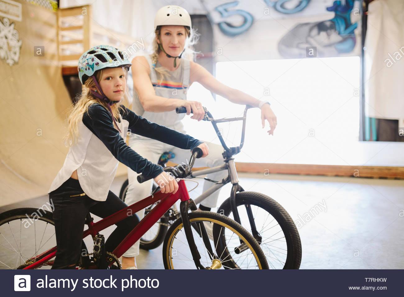 Ritratto fiducioso madre e figlia con biciclette BMX a indoor skate park Immagini Stock