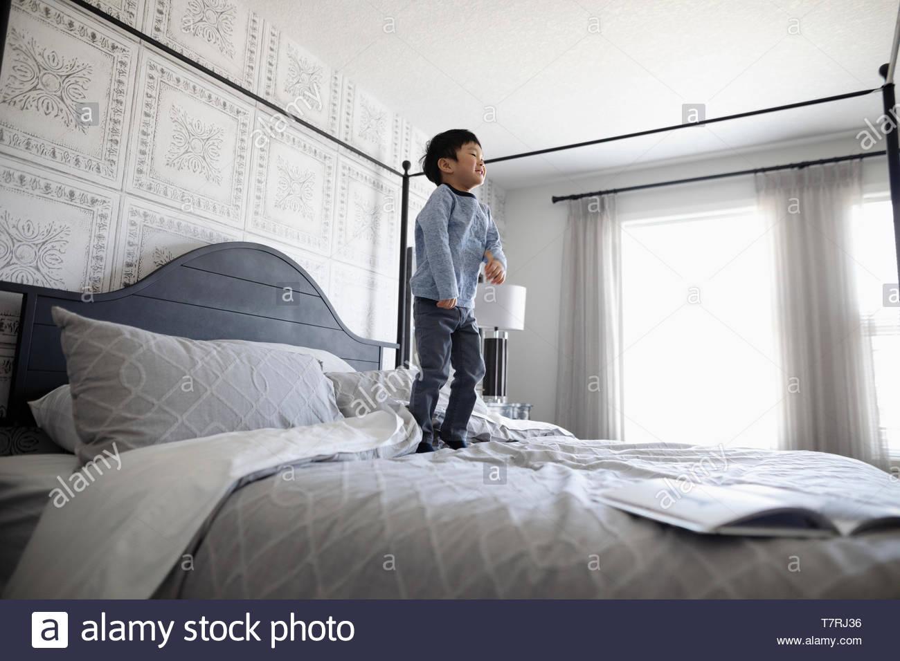 Giocoso ragazzo saltando sul letto Immagini Stock