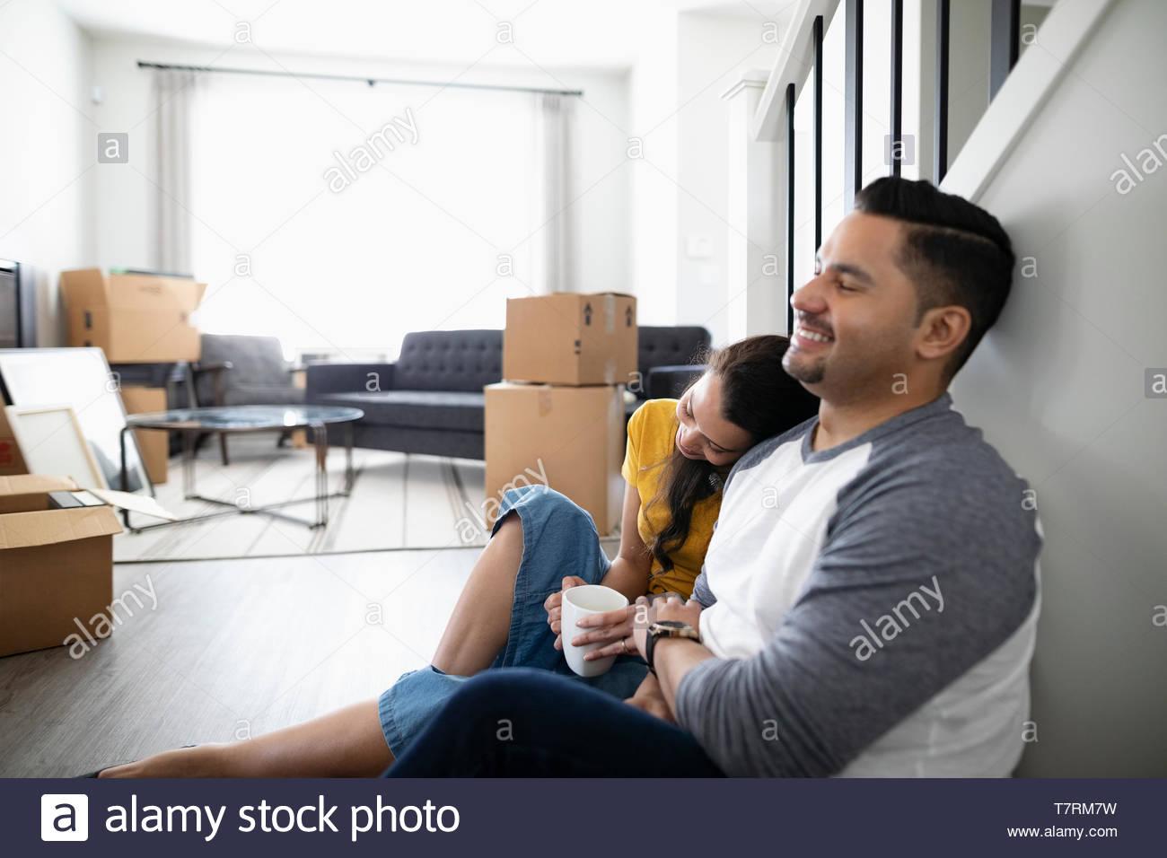 Affettuoso, coppia felice di prendere una pausa dal movimento, bere il caffè sul pavimento Immagini Stock