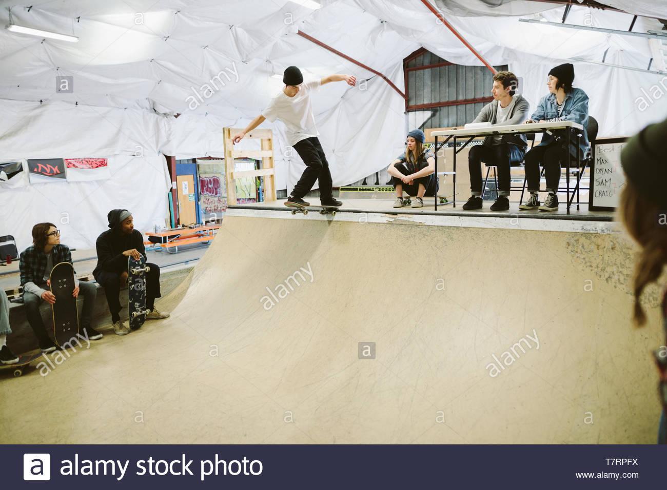 I giudici a guardare lo skateboard la concorrenza nella parte superiore della rampa a indoor skate park Immagini Stock