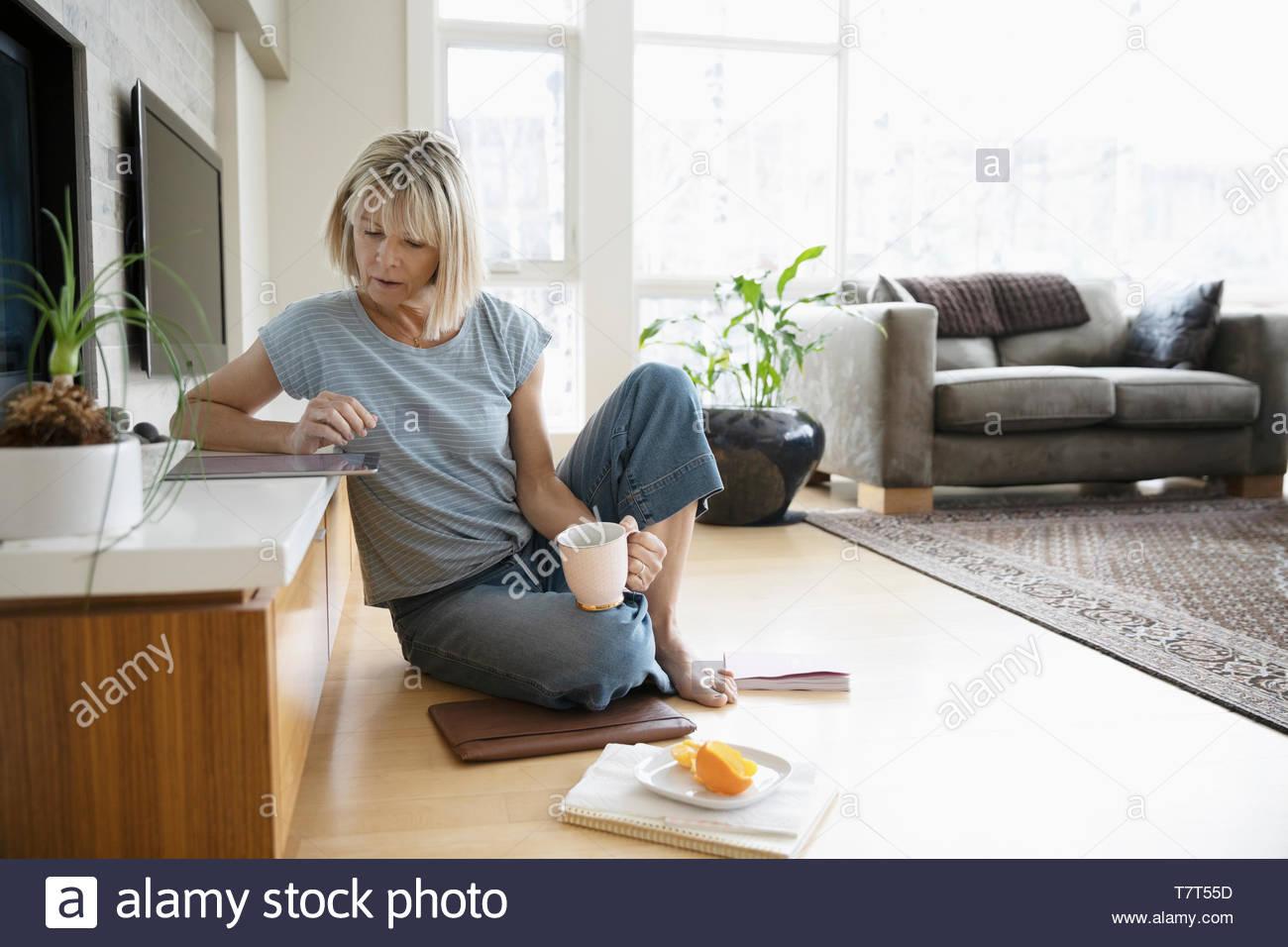 La donna che lavora da casa, usando tavoletta digitale sul soggiorno piano Immagini Stock