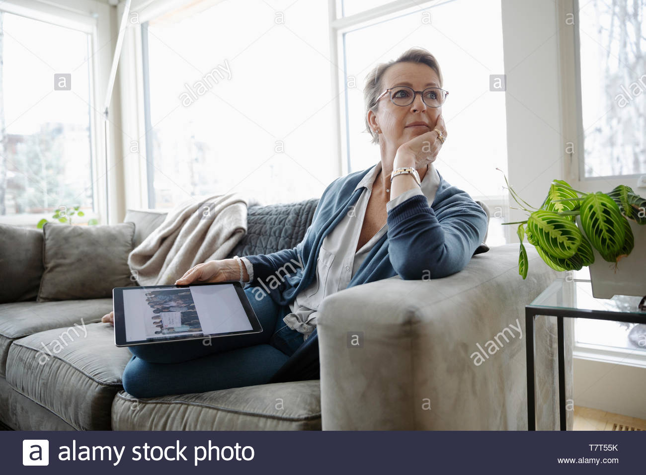 Premurosa donna matura con tavoletta digitale sul divano Immagini Stock