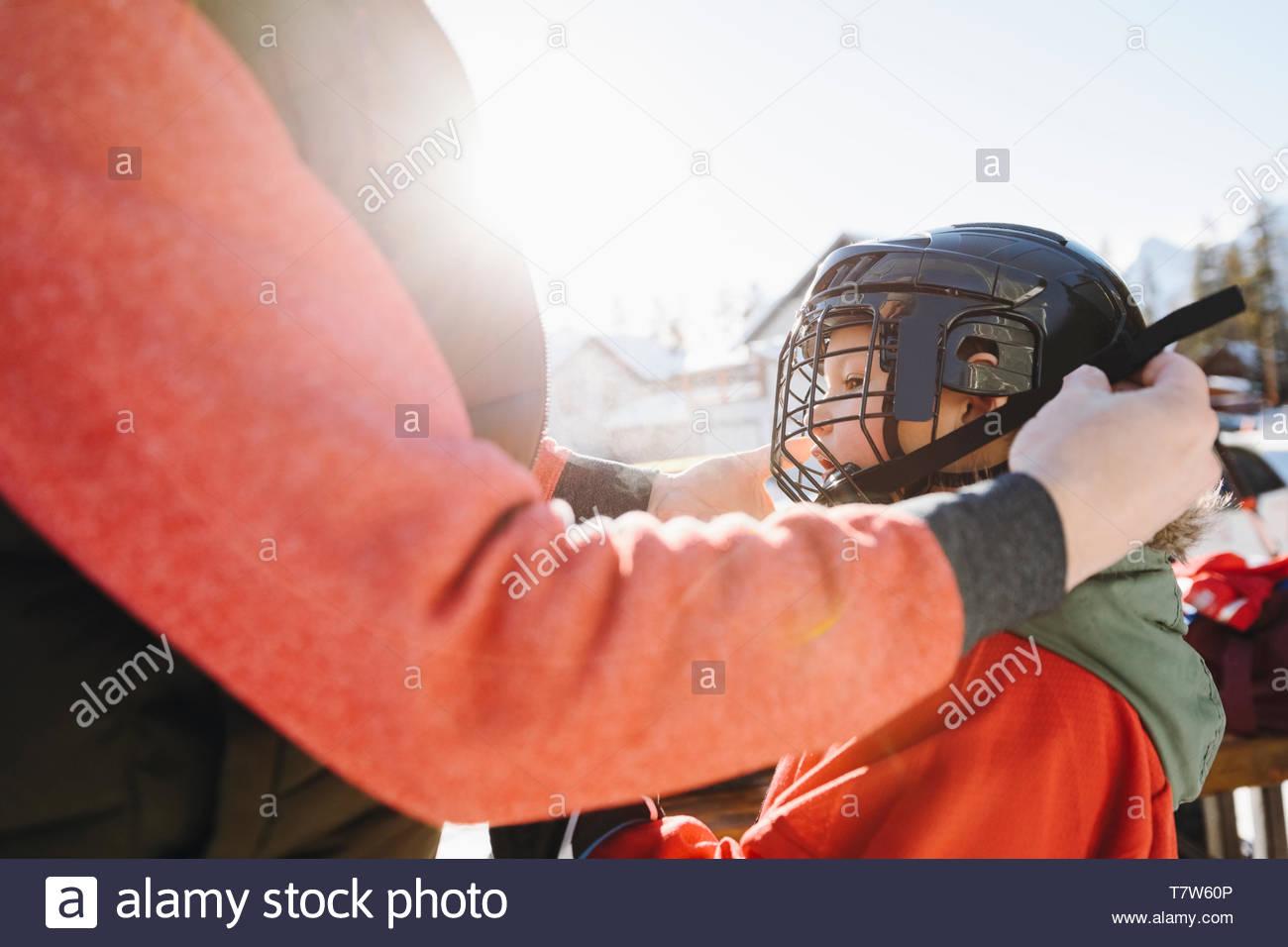 Padre figlio di fissaggio della outdoor ice hockey Casco Immagini Stock
