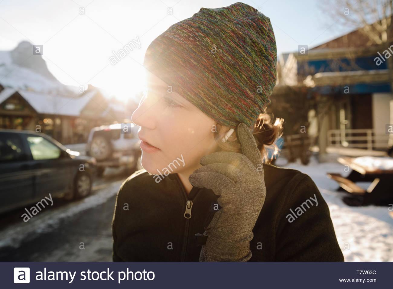 Ragazza adolescente runner cuffie di regolazione sul soleggiato, snowy marciapiede Immagini Stock