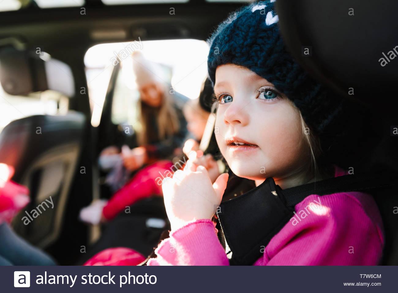 Carino il toddler ragazza nel sedile posteriore della macchina Immagini Stock