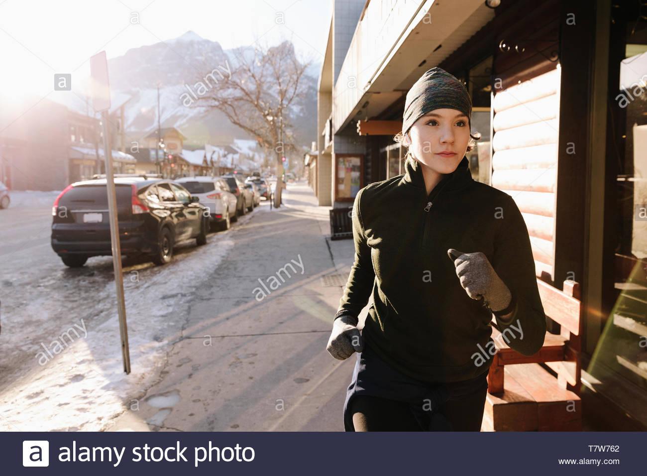 Focalizzato ragazza adolescente che corre lungo inverno pieno di sole marciapiede Immagini Stock