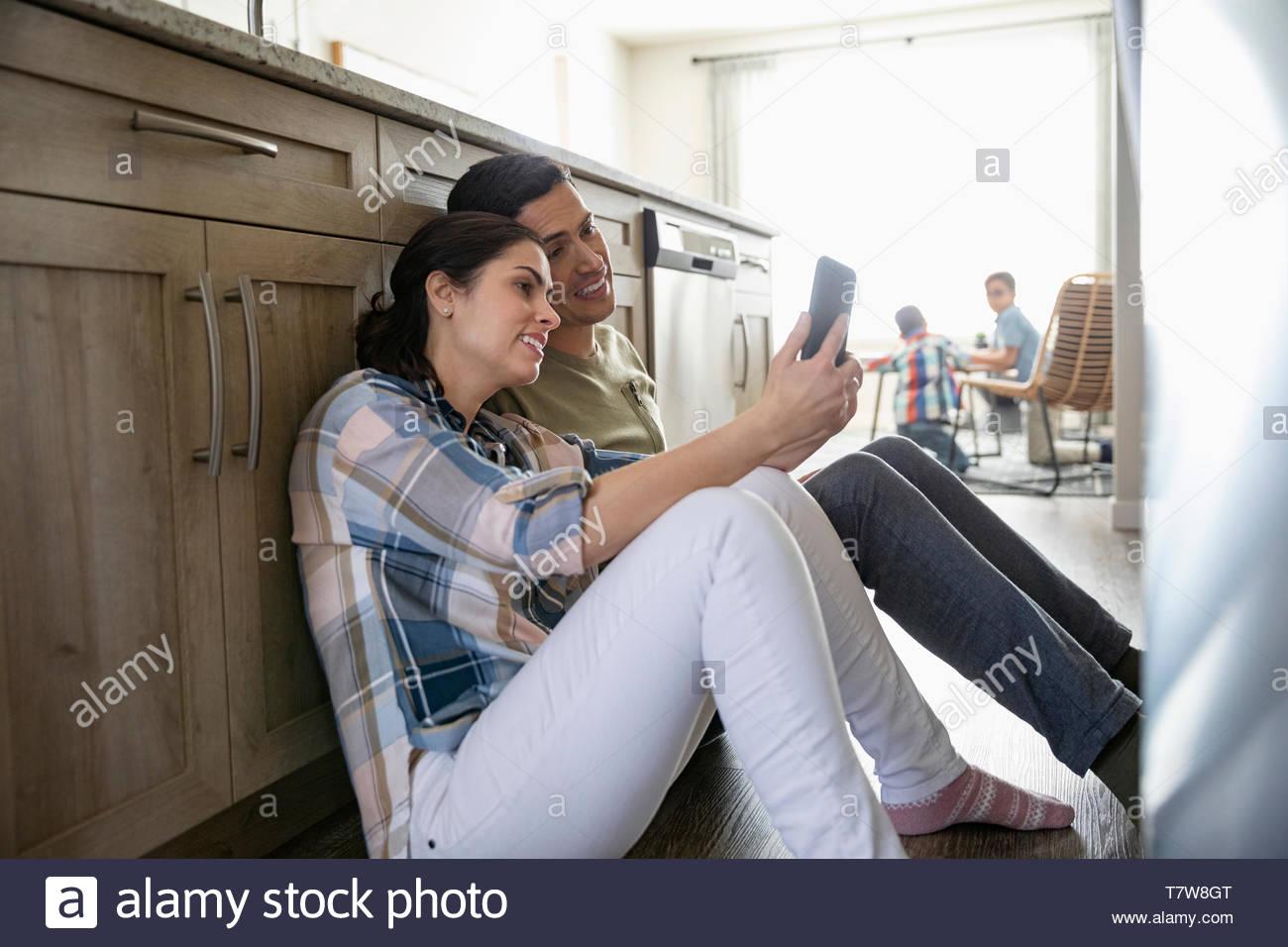 Affettuosa giovane utilizzando smart phone sul pavimento della cucina con i bambini in background Immagini Stock
