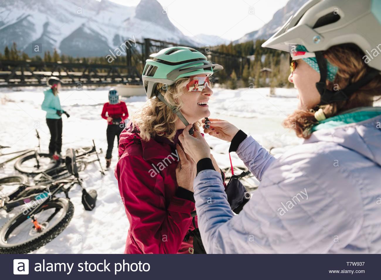Donna amico di fissaggio del casco, la preparazione per il grasso in bici nella neve Foto Stock