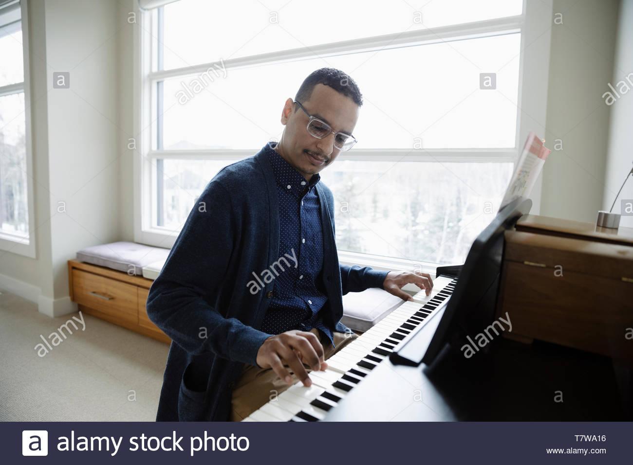 L'uomo suonare il pianoforte a casa Immagini Stock