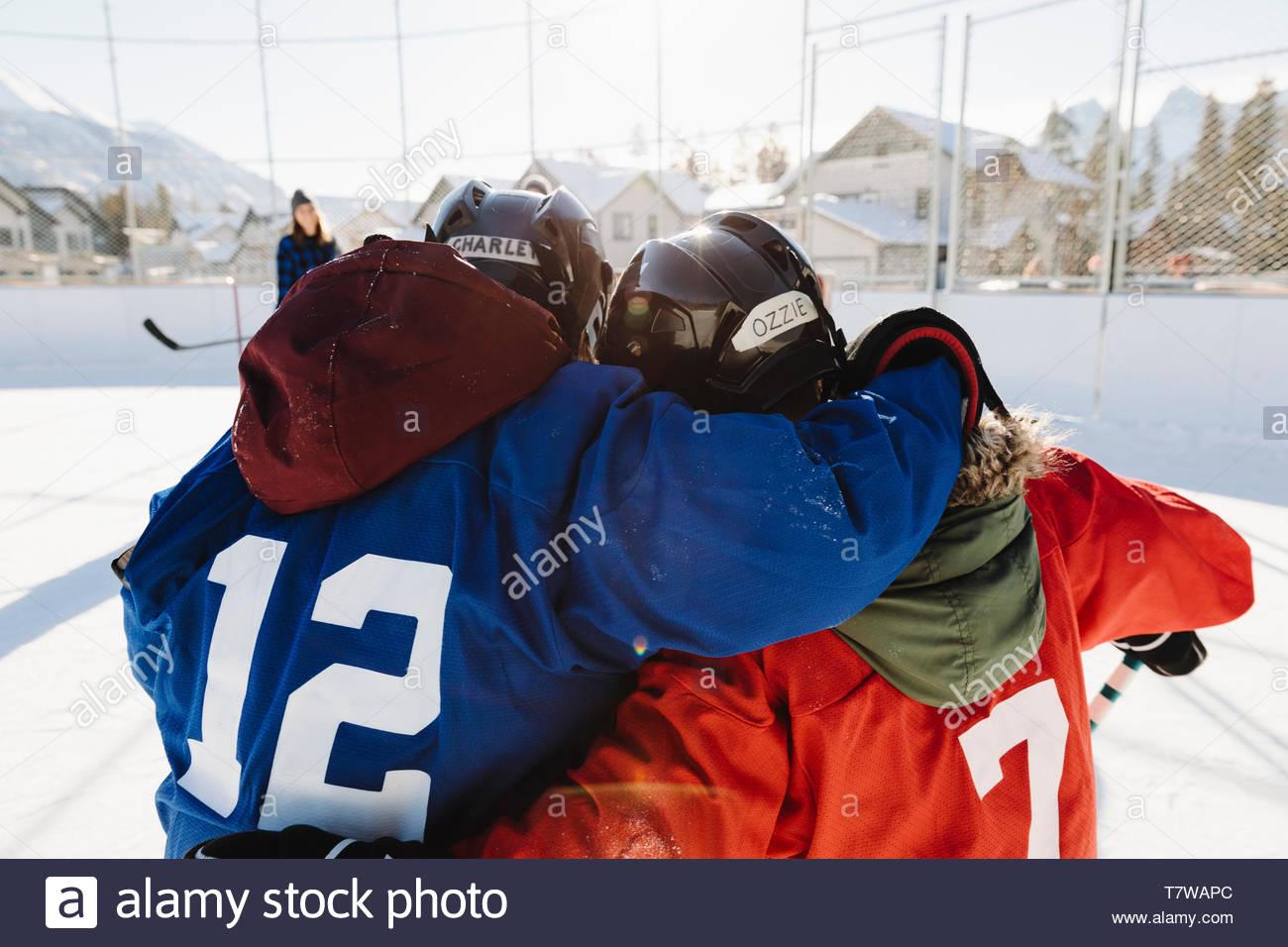 Amici, abbracciando la riproduzione esterna di hockey su ghiaccio Immagini Stock