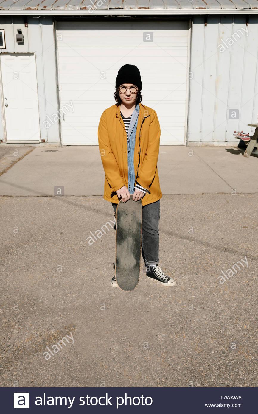 Femmina fiducioso guidatore di skateboard in posa nella soleggiata area di parcheggio Immagini Stock