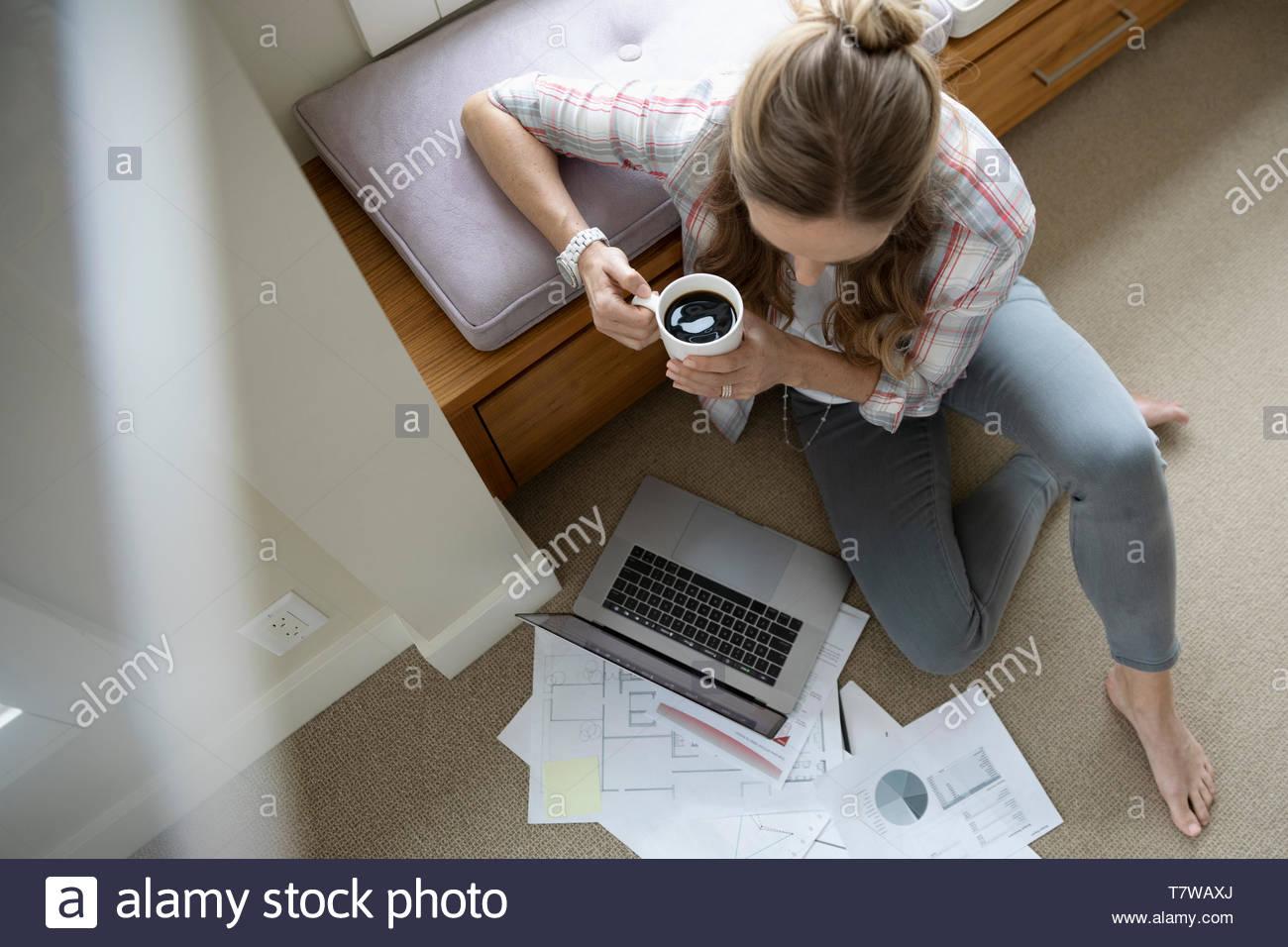 Vista da sopra la donna che lavora da casa, utilizzando laptop e di bere il caffè sul pavimento Immagini Stock