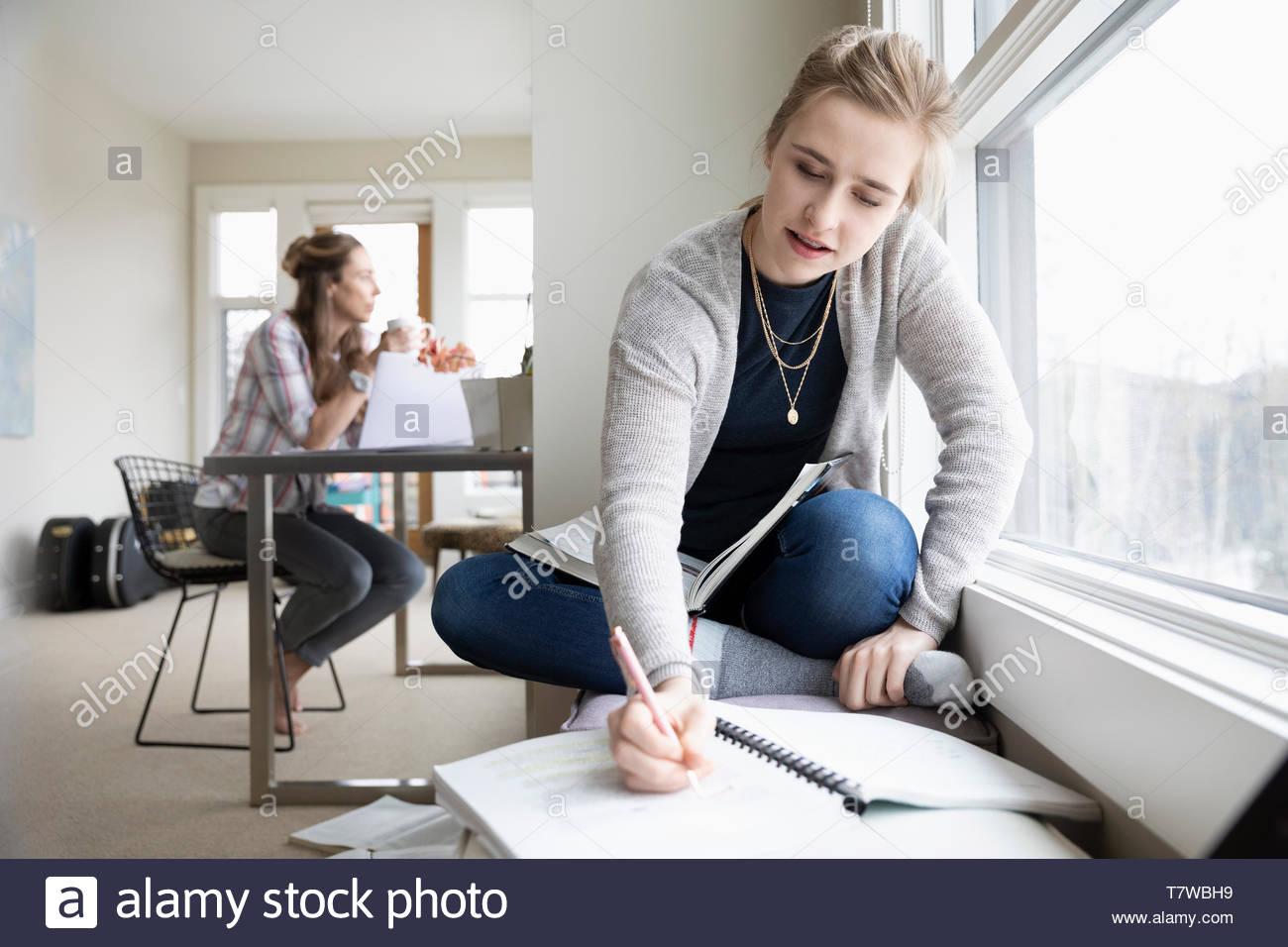 Ragazza adolescente facendo compiti a casa mentre la madre lavora in background Immagini Stock