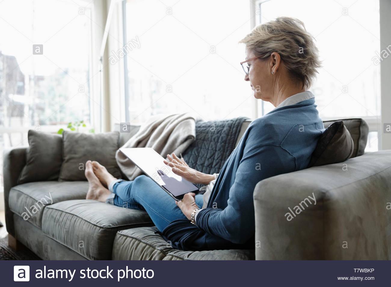 Donna matura con tavoletta digitale sul divano Immagini Stock