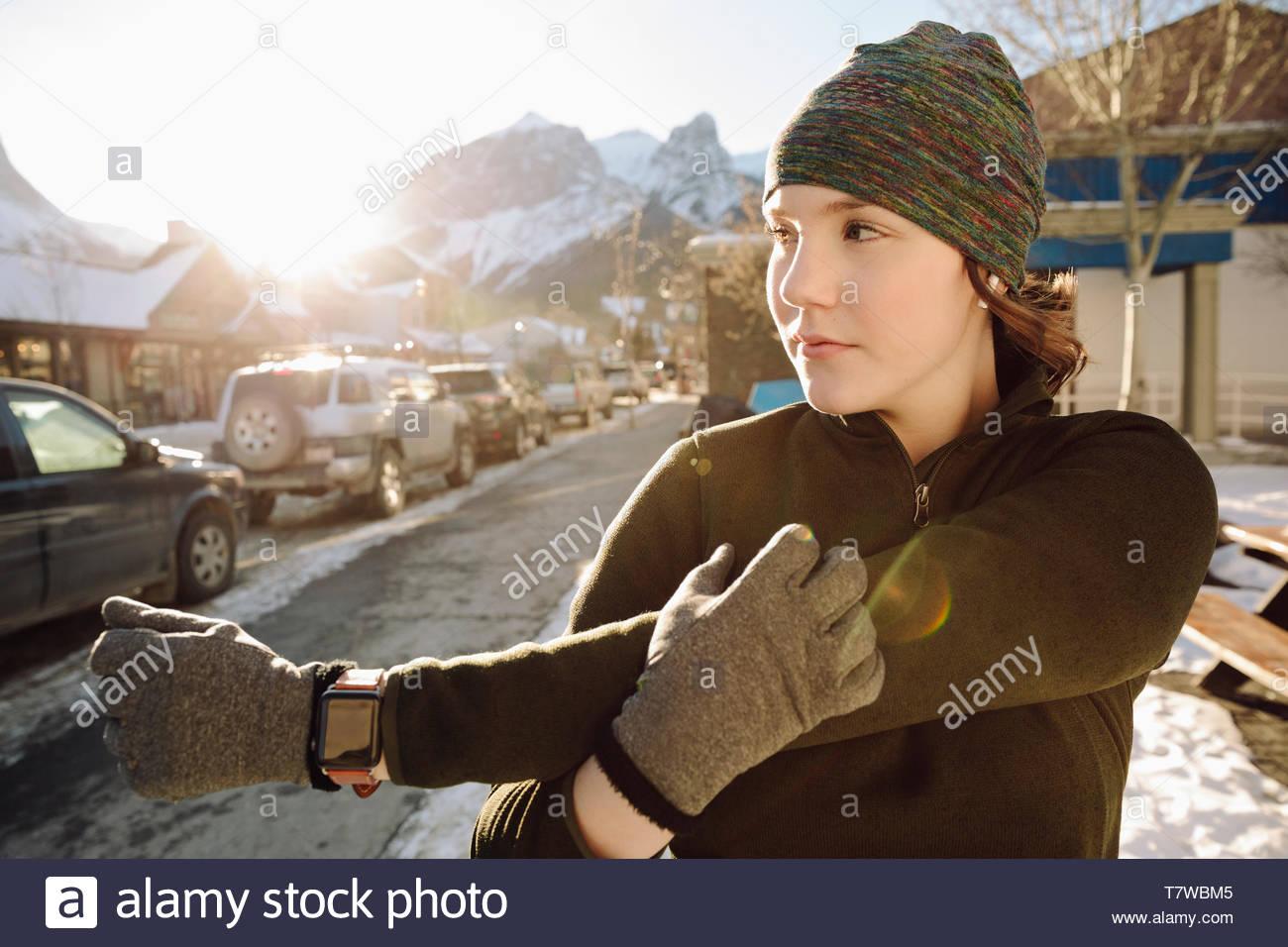 Ragazza adolescente runner braccio di stiro sul marciapiede in inverno Immagini Stock