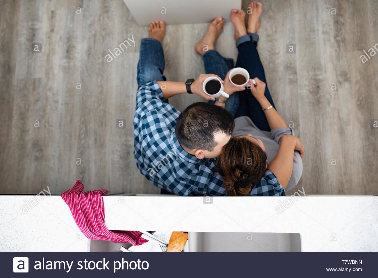 Vista da sopra affettuosa paio di bere il caffè sul pavimento della cucina sotto lavello Immagini Stock