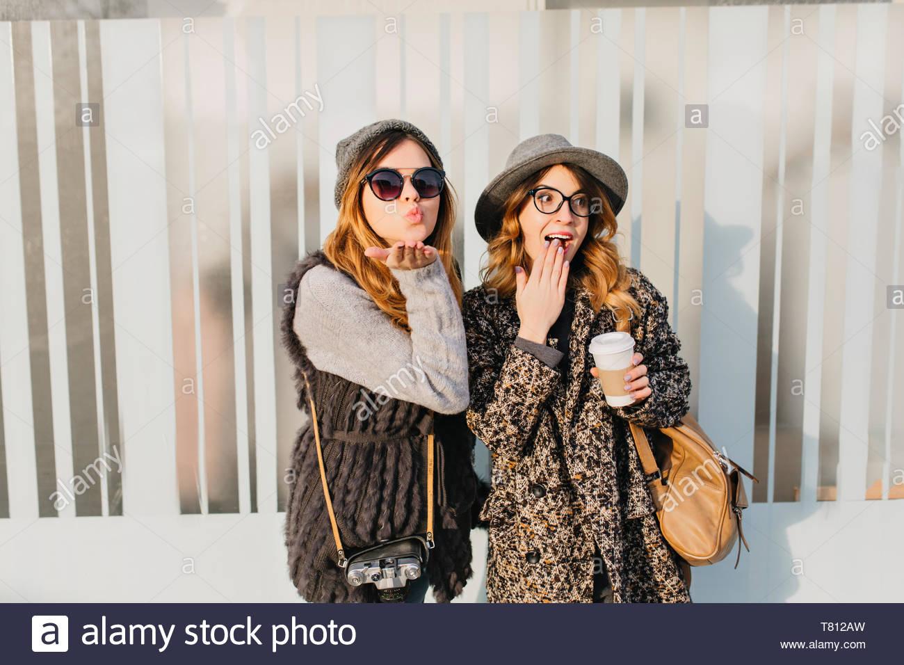 Ritratto di due eleganti funny felice ragazze divertirsi sulle strade della città. Giornata soleggiata della elegante giovane donna che viaggiano insieme, esprimendo una positività, emozioni vere e giocoso, godendo del sole e sorridente Immagini Stock